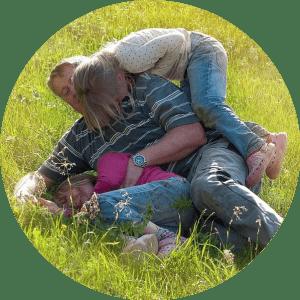 Un papa qui joue avec ses deux fille dans un espace vert